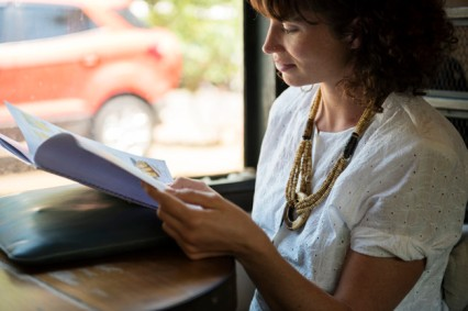 Woman reading magazine at coffee shop
